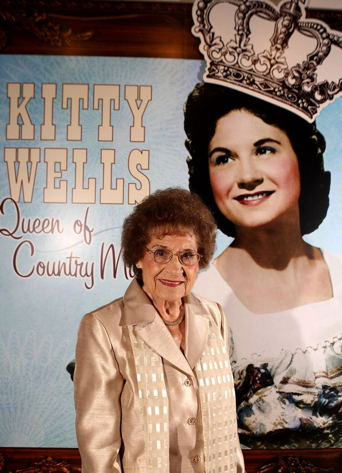Photo -   FILE - This Aug. 14, 2008 file photo originally released by the Country Music Hall of Fame and Museum shows music pioneer Kitty Wells at an exhibit honoring her career in Nashville, Tenn. Wells, the first female superstar of country music, has died at the age of 92. The singer's family says Wells died at her home Monday after complications from a stroke. Her recording of