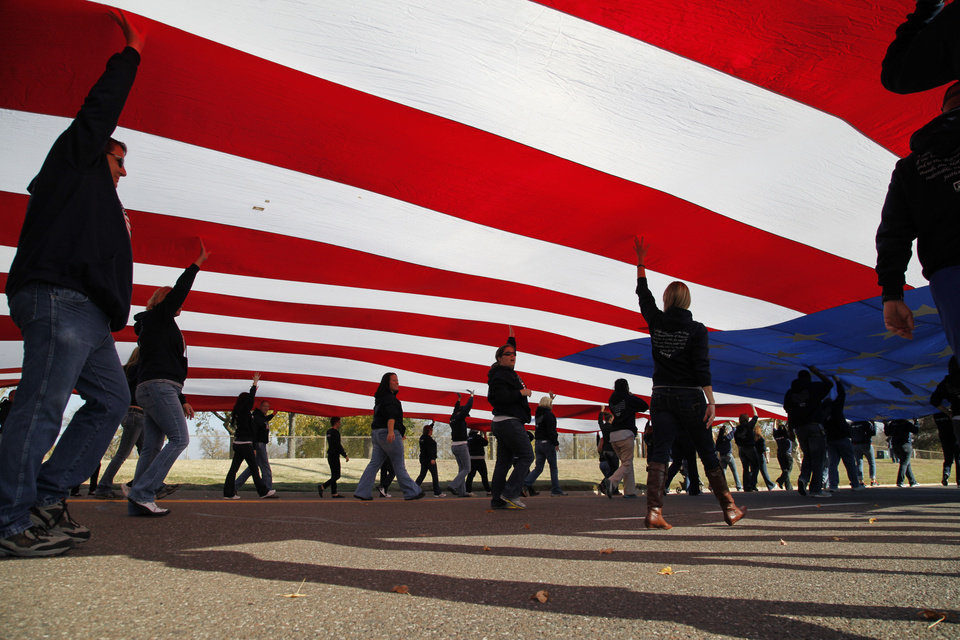Members of the Tinker Federal Credit Union carry a large American flag during a Veterans Day parade on SE 15th St. in Midwest City, OK, Monday, November 11, 2013, Photo by Paul Hellstern, The Oklahoman