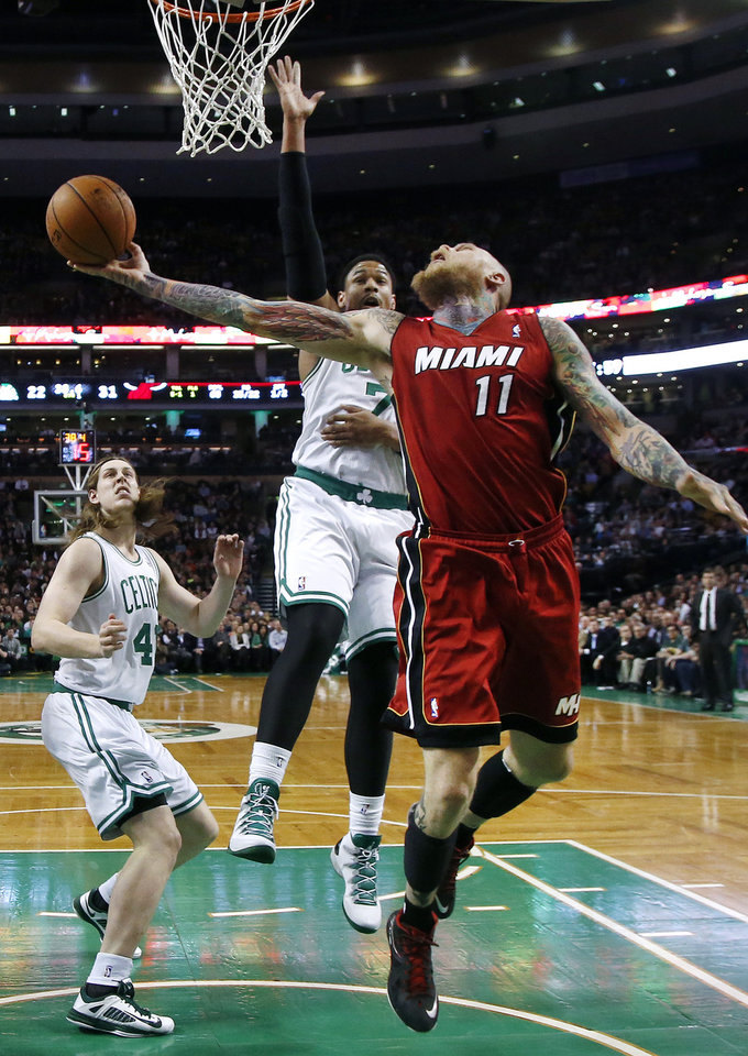Photo - Miami Heat forward Chris Andersen (11) stretches to make a layup against Boston Celtics forward Jared Sullinger (7) and center Kelly Olynyk (41) during the first quarter of an NBA basketball game in Boston on Wednesday, March 19, 2014. (AP Photo/Elise Amendola)