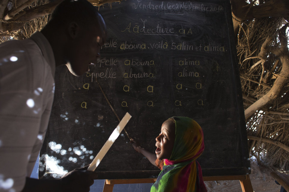 "In this Nov. 2, 2012 photo, teacher Djobelsou Guidigui Eloi, left, scolds a girl unable to read out a lesson on the sound of the letter 'a' in the village of Louri in the Mao region of Chad. Many of the children, unable to read, attempted to pass the lesson by memorizing the sounds and their order on the blackboard. A survey conducted in the country found that 51.9 percent of the children are stunted, one of the highest rates in the world according to a summary published by UNICEF. Stunting is the result of having either too few calories, too little variety, or both. The struggle that is on display every day in the village's one-room schoolhouse reveals not only the staggering price that these children are paying, but also the price that it has exacted from Africa. (AP Photo/Rebecca Blackwell) PART OF A 16-PICTURE PACKAGE WITH THE STORY ""CHAD STUNTED NATION"" ORG XMIT: NY871"