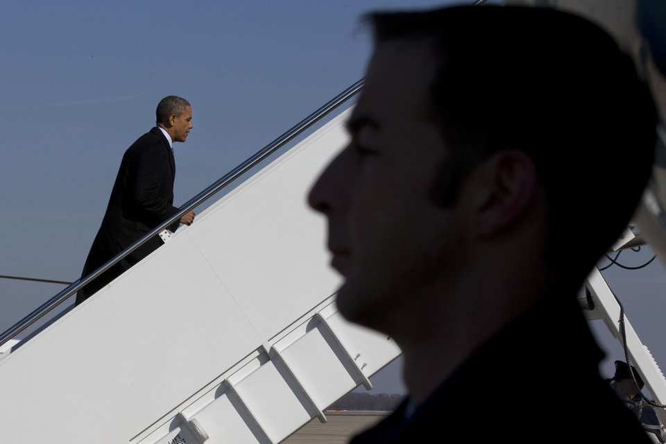 Photo - President Barack Obama boards Air Force One at Andrews Air Force Base, Md., Friday, Feb. 7, 2014, prior to departure to Michigan where he is expected to speak about the farm bill.  (AP Photo/Jacquelyn Martin)