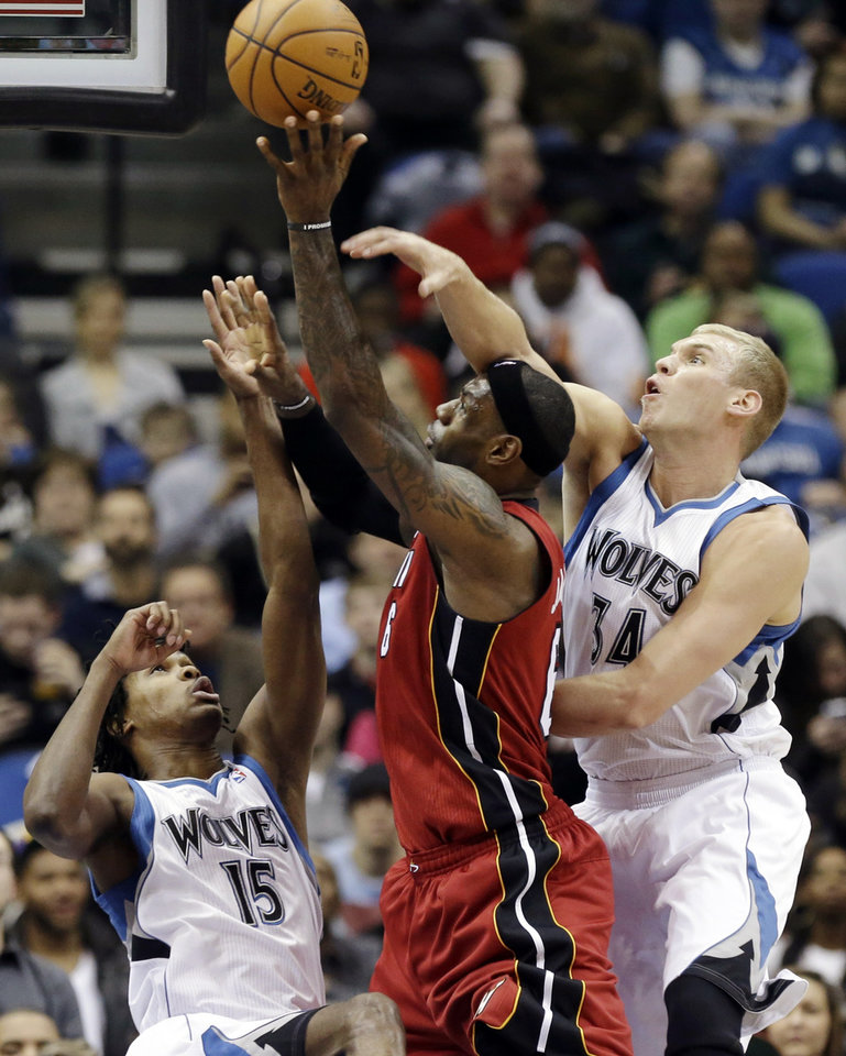 Photo - Miami Heat's LeBron James shoots as Minnesota Timberwolves' Greg Stiemsma, right, and Mikael Gelabale, left, of France, defend in the first half of an NBA basketball game, Monday, March 4, 2013, in Minneapolis. (AP Photo/Jim Mone)