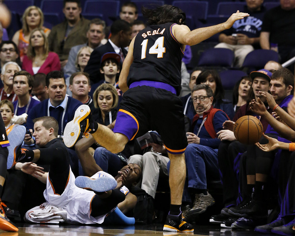 Photo - Oklahoma City Thunder's Kevin Durant, bottom left, collides with Phoenix Suns' Luis Scola (14), of Argentina, as both go after a loose ball during the first half in an NBA basketball game, Sunday, Feb. 10, 2013, in Phoenix. (AP Photo/Ross D. Franklin)