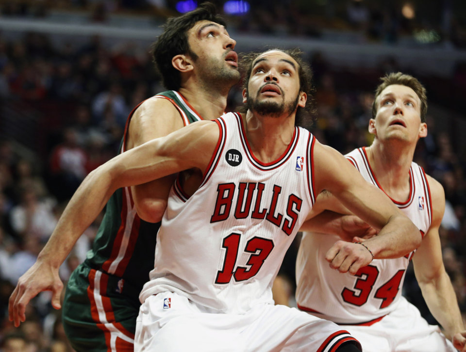 Photo - FILE - In this April 4, 2014 file photo, Chicago Bulls center Joakim Noah (13) defends against Milwaukee Bucks center Zaza Pachulia during an NBA basketball game in Chicago.  A person familiar with the situation says that Noah is the NBA's Defensive Player of the Year. The person spoke Monday, April 21, 2014 on the condition of anonymity because the award had not been announced. (AP Photo/Kamil Krzaczynski, File)