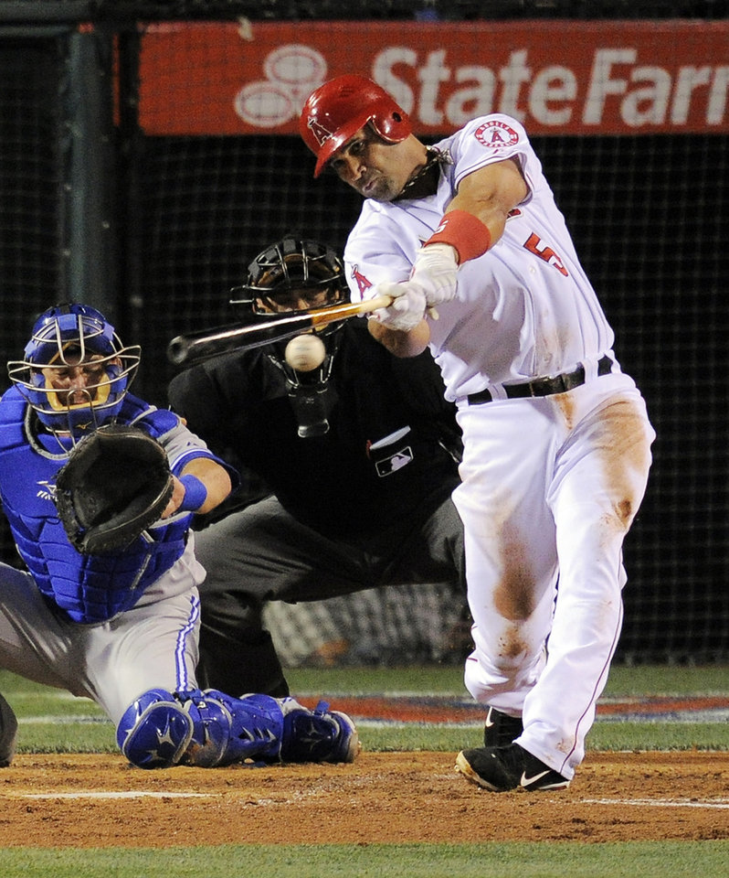Photo -   Los Angeles Angels' Albert Pujols, lines out to the shortstop as Toronto Blue Jays catcher Jeff Mathis watches during the fourth inning of their baseball game, Friday, May 4, 2012, in Anaheim, Calif. (AP Photo/Mark J. Terrill)