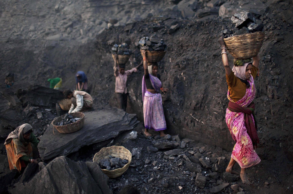Photo -   FILE - In this Jan. 7, 2011 file photo, people carry baskets of coal scavenged illegally at an open-cast mine in the village of Bokapahari in the eastern Indian state of Jharkhand where a community of coal scavengers live and work. India's national auditor said Friday, Aug. 17, 2012, the government lost huge sums of money by selling coal fields to private companies without competitive bidding, adding to massive losses from dubious auctions of other state assets. The Comptroller and Auditor General's report to Parliament estimated that private companies got a windfall profit of $34 billion because of the low prices they paid for the fields.(AP Photo/Kevin Frayer, File)