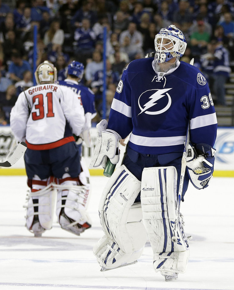 Photo - Tampa Bay Lightning goalie Anders Lindback (39), of Sweden, and Washington Capitals goalie Philipp Grubauer (31), of Germany, switch ends of the ice midway through the second period of an NHL hockey game Thursday, Jan. 9, 2014, in Tampa, Fla. The teams changed ends due to poor ice. (AP Photo/Chris O'Meara)