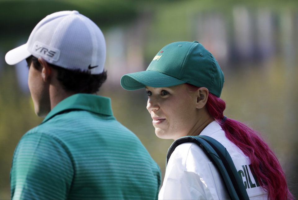 Photo - Rory McIlroy, of Northern Ireland, walks with his fiancee and tennis player Caroline Wozniacki after Wozniacki putted on the ninth hole during the par three competition at the Masters golf tournament Wednesday, April 9, 2014, in Augusta, Ga. (AP Photo/David J. Phillip)