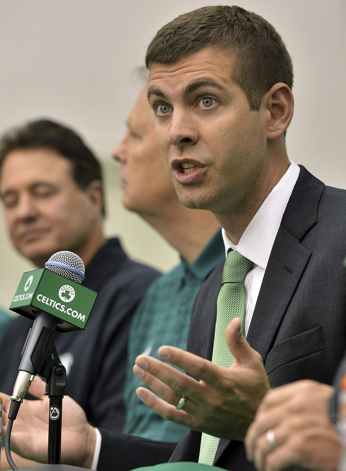 Photo - New Boston Celtics head coach Brad Stevens speaks during a news conference Friday, July 5, 2013, at the NBA Basketball team's training facility in Waltham, Mass. Sitting alongside are Celtics co-owner Stephen Pagliuca, left, and general manager Danny Ainge, second from right. Stevens, who twice led the Butler Bulldogs to the NCAA title game, replaces Doc Rivers, who was traded to the Los Angeles Clippers. (AP Photo/Josh Reynolds)
