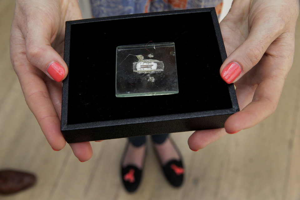 Photo - FILE - In this May 23, 2014 file photo, an employee of the Christie's auction house poses for photographs with a 1958 prototype integrated circuit mounted on glass designed by Nobel Prize Physics winner Jack Kilby at Texas Instruments, at premises of the auction house in London, Friday, May 23, 2014.  The prototype microchip, a historical contribution to the modern computing era, is estimated to fetch between $1,000,000 and $2,000,0000 at a June 19 sale in New York.  (AP Photo/Matt Dunham, File)