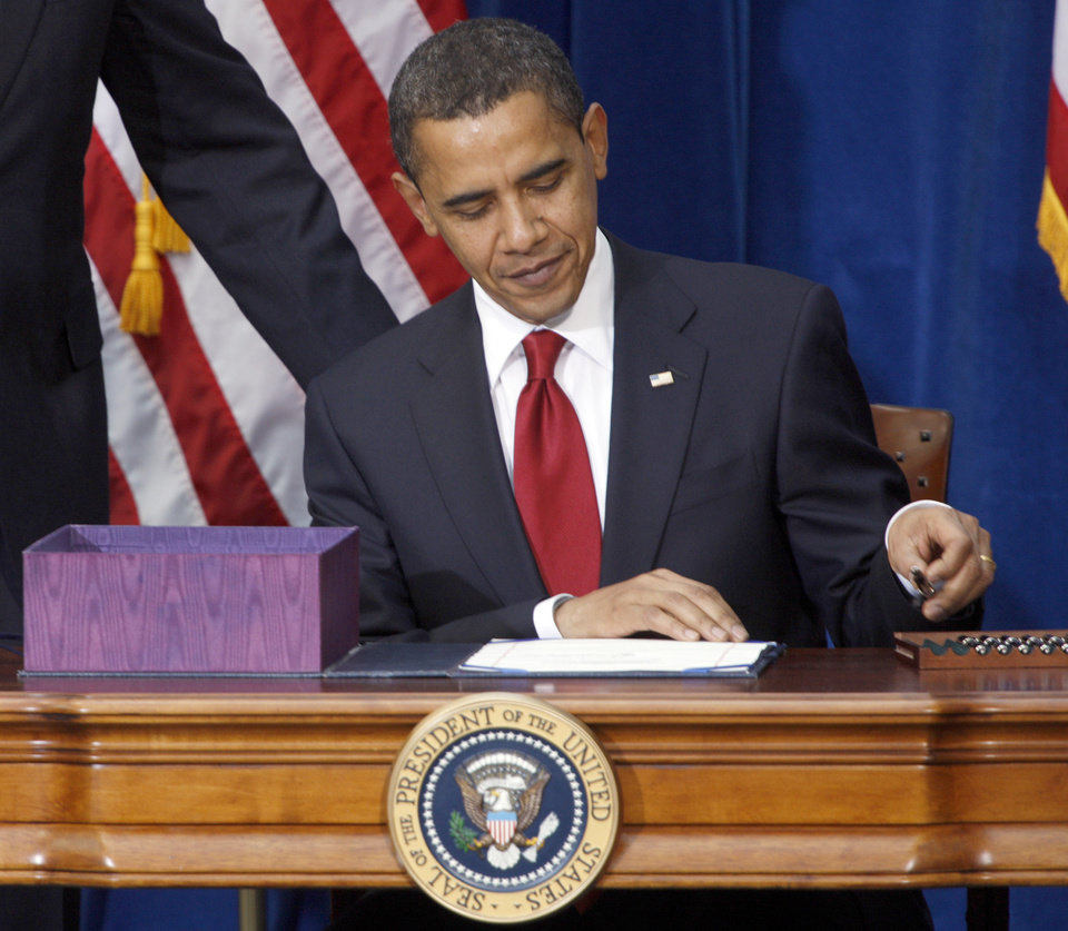 FILE This Feb. 17, 2009 file photo shows President Barack Obama picking up the first pen to sign the economic stimulus bill during a ceremony in the Museum of Nature and Science in Denver. The White House says a costly spending bill President Barack Obama signed into law five years ago Monday was good for the economy and helped the U.S. avoid another Great Depression. (AP Photo/David Zalubowski, File)
