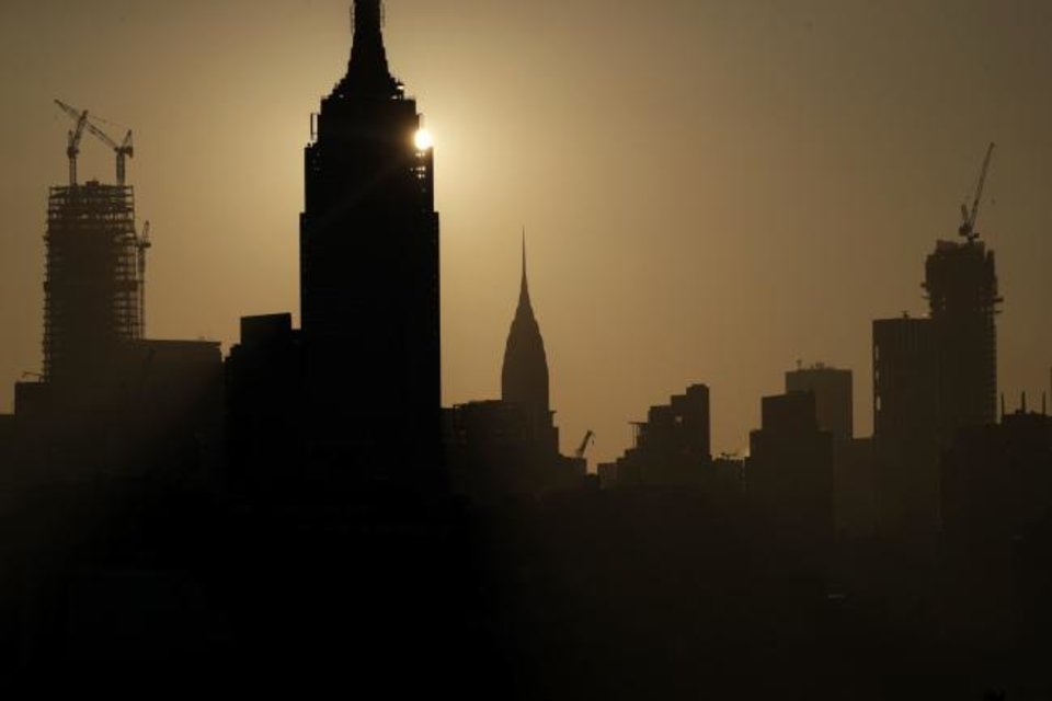 Photo -  The rising sun peeks on the side of the Empire State Building seen from Jersey City, N.J. [AP PHOTO]