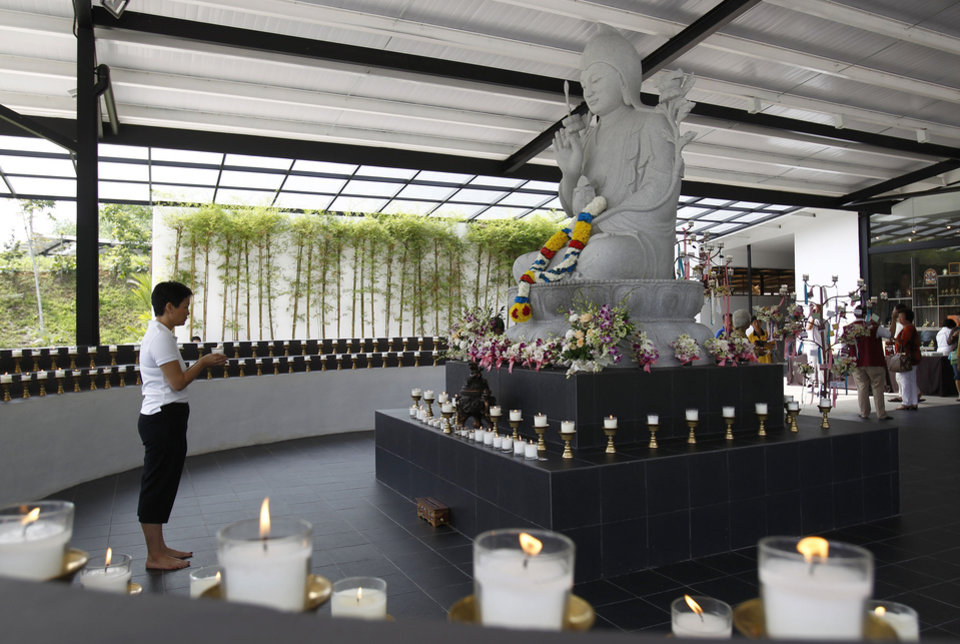 Photo - A Buddhist devotee holds a candle while offering prayers for passengers onboard the missing Malaysia Airlines Flight 370 at Kechara Forest Retreat in Bentong, outside Kuala Lumpur, Malaysia, Sunday, April 13, 2014. After a week of optimism over four underwater signals believed to be coming from the missing Malaysian plane, the sea has gone quiet and Australia's leader is warning that the massive search will likely be long. (AP Photo/Lai Seng Sin)