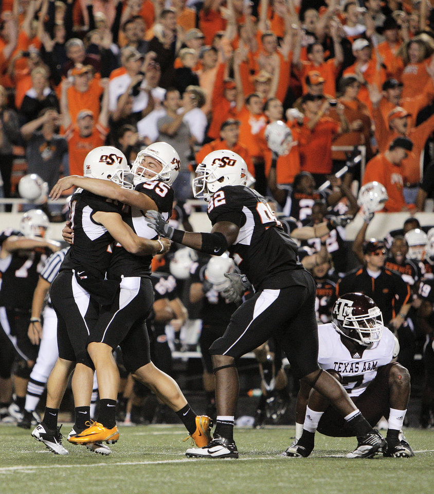 Photo - From left, OSU's Wes Harlan (11), Dan Bailey (95) and Darius Hart (92) celebrate near Texas A&M's Terrence Frederick (7) after Bailey kicked the game-winning field goal at the end of the college football game between Texas A&M University and Oklahoma State University (OSU) at Boone Pickens Stadium in Stillwater, Okla., Thursday, Sept. 30, 2010. OSU won, 38-35. Photo by Nate Billings, The Oklahoman