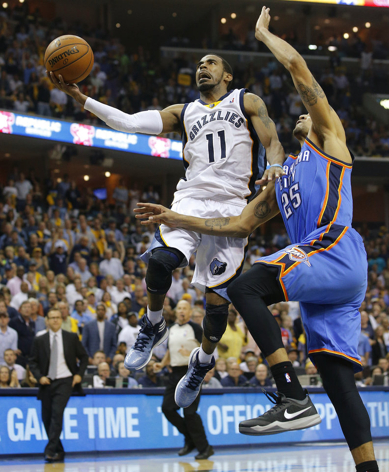 Photo - Memphis' Mike Conley (11) goes past Oklahoma City's Thabo Sefolosha (25) during Game 3 in the first round of the NBA playoffs between the Oklahoma City Thunder and the Memphis Grizzlies at FedExForum in Memphis, Tenn., Thursday, April 24, 2014. Memphis won 98-95. Photo by Bryan Terry, The Oklahoman