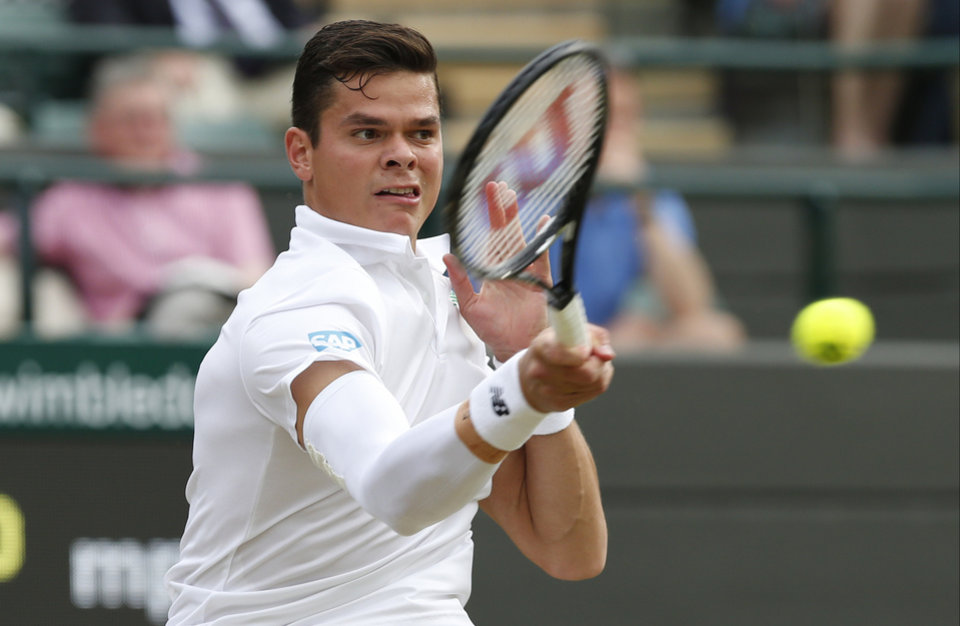 Photo - Milos Raonic of Canada plays a return to Nick Kyrgios of Australia during their men's singles quarterfinal match at the All England Lawn Tennis Championships in Wimbledon, London, Wednesday, July 2, 2014. (AP Photo/Ben Curtis)