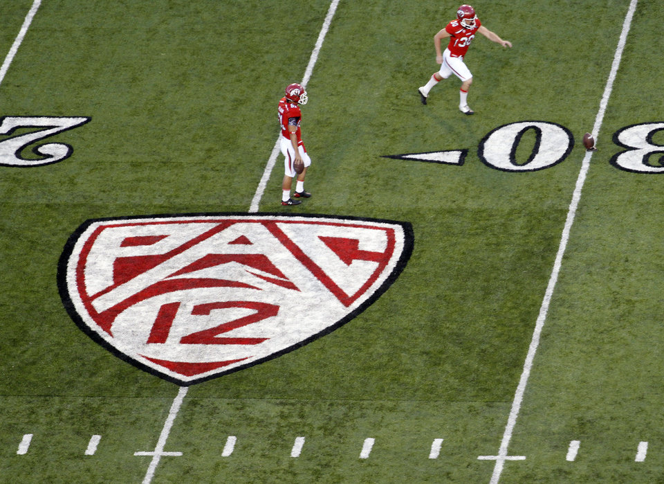 FILE- in this Sept. 1, 2011 file photo, a Pac 12 insignia is painted on the field as Utah players warm up before the second half of an NCAA college football game against the Montana State at Rice-Eccles Stadium in Salt Lake City. The Pac-12 gained attention over the weekend with more talk of Oklahoma and Texas possibly heading West to form a super conference. On the field, the news wasn't quite so encouraging, filled with embarrassing losses and lackluster wins. (AP Photo/Jim Urquhart) ORG XMIT: NY167