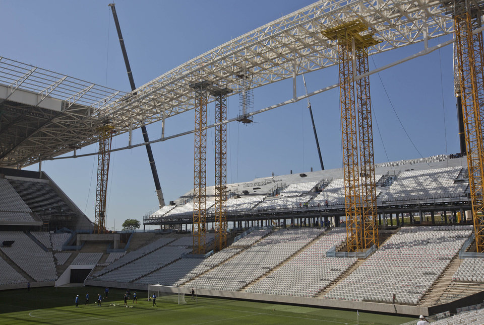 Photo - FILE - In this March 15, 2014 file photo, Brazilian club Corinthians soccer players practice at the Itaquerao stadium in Sao Paulo, Brazil.   Brazilian organizers are adding safety features where a worker died in the stadium hosting the World Cup opener, hoping to quickly reverse an order that halted construction in part of the venue. The addition of new safety rails comes a day after labor officials said the installation of 20,000 temporary seats at the Itaquerao stadium could not continue until safety concerns were addressed. On Saturday March 29th,  2014, a 23-year-old worker died after falling from about 26 feet while installing the seats needed for the opener. (AP Photo / Andre Penner, File)