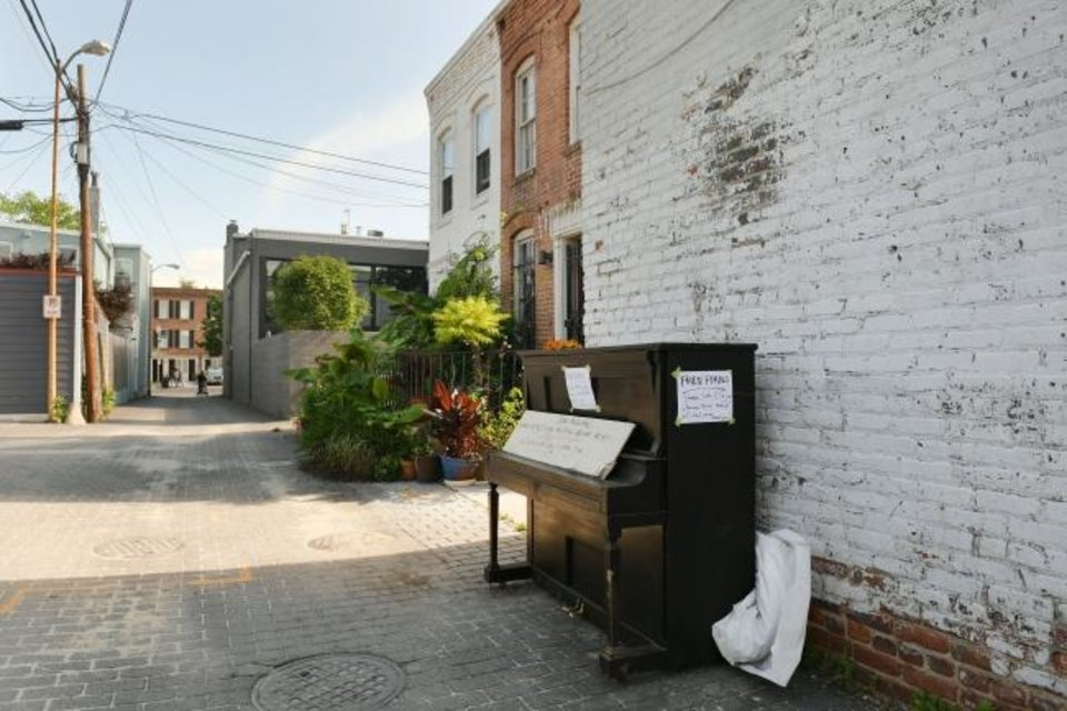 Photo -  An abandoned piano sits in a Capitol Hill alley, free for the taking, on May 21. Its sign says