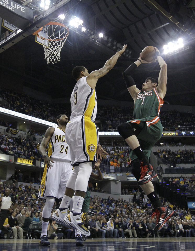 Photo - Milwaukee Bucks' Ersan Ilyasova (7) shoots against Indiana Pacers' George Hill (3) during the first half of an NBA basketball game on Thursday, Feb. 27, 2014, in Indianapolis. (AP Photo/Darron Cummings)