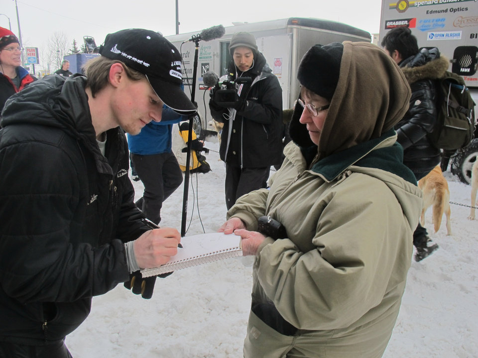 Defending champion Dallas Seavey, left, signs an autograph for Bunky Nistler of Beach, N.D., before the ceremonial start of the 2013 Iditarod Trail Sled Dog Race in Anchorage, Alaska on Saturday, March 2, 2013. The race, which will take mushers about a thousand miles across the Alaska wilderness, starts Sunday, March 3, 2013, in Willow, Alaska. (AP Photo/Mark Thiessen)