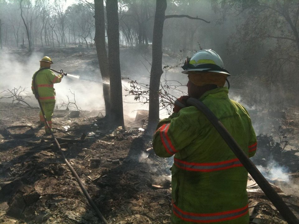Photo - Tuttle firefighters dose hot spots near NE 66th and Sooner Rd.  Photo by Jim Beckel, The Oklahoman.