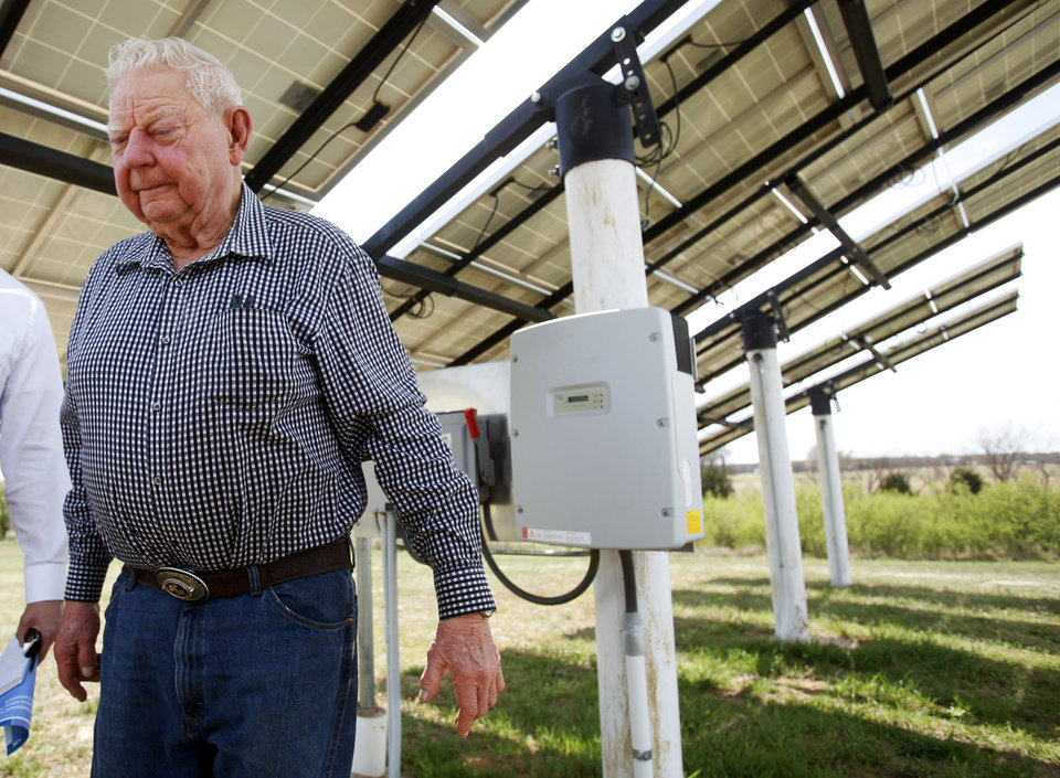 Photo -  Herb Hill walks away from the shadows of the solar panels he installed at his home in Crescent.Photo by KT King, The Oklahoman   KT King -