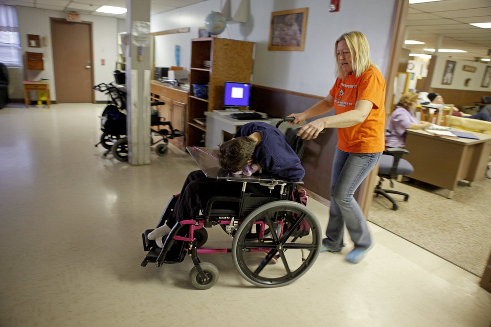Photo - Lisa White takes a resident to lunch inside the Northern Oklahoma Resource Center in Enid.  BRYAN TERRY