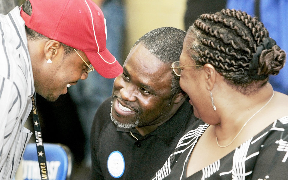 Gerald McCoy, left, and his parents talk after he signed with OU in 2006. Photo By Nate Billings, The Oklahoman archive