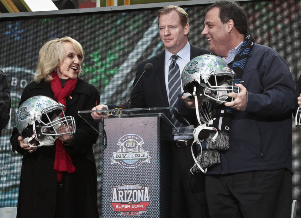 Photo - NFL Commissioner Roger Goodell, center, stands between Arizona Gov. Jan Brewer, left, and New Jersey Gov. Chris Christie, right, showoff souvenir football helmets after a ceremony to pass official hosting duties of next year's Super Bowl to Arizona, Saturday Feb. 1, 2014 in New York.   (AP Photo/Bebeto Matthews)