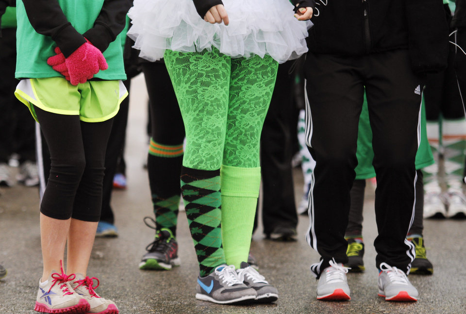 Photo - Spectators stand wearing St. Patrick's Day decor during the Shamrock Shuffle 5K Race/Walk in Hartford, Wis.  on Saturday, March 16, 2013. Proceeds from the race benefited the Hartford Union Varsity Club.  (AP Photo/The Daily News, John Ehlke)