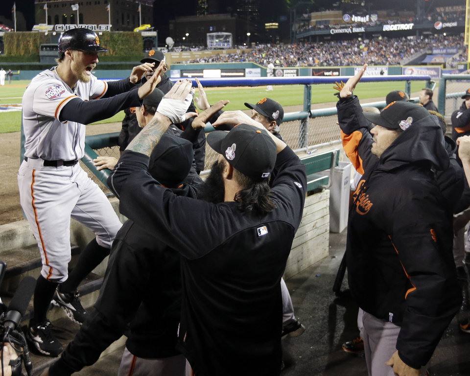 Photo -   San Francisco Giants' Hunter Pence is congratulated in the dugout after scoring on a triple by Gregor Blanco during the second inning of Game 3 of baseball's World Series against the Detroit Tigers Saturday, Oct. 27, 2012, in Detroit. (AP Photo/David J. Phillip)
