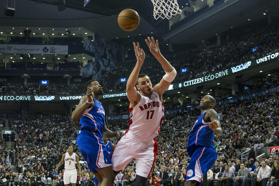 Photo - Toronto Raptors' Jonas Valanciunas, center, looses control of the ball after being fouled by Los Angeles Clippers DeAndre Jordan, left, as Clippers' Jamal Crawford looks on during the first half of an NBA basketball game, Saturday, Jan. 25, 2014 in Toronto. (AP Photo/The Canadian Press, Chris Young)