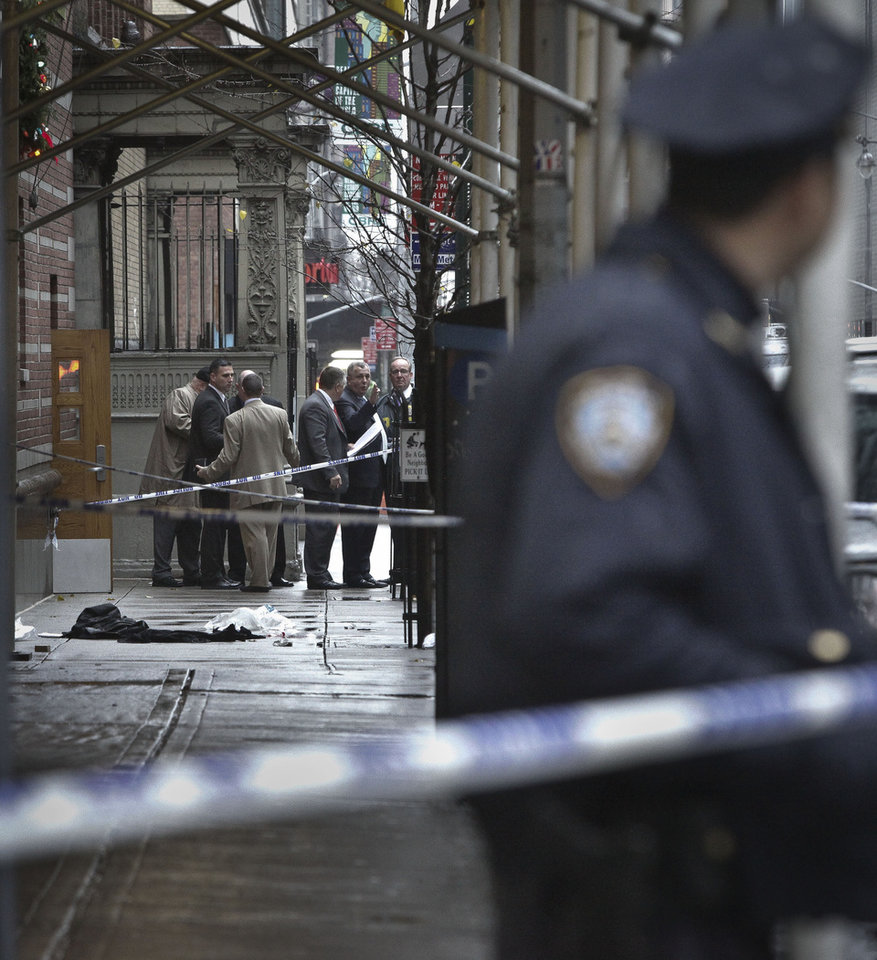 Photo - Police investigate the scene where a man was fatally shot in the back of the head in New York on Monday, Dec. 10, 2012. Authorities said the man was shot outside a school near Columbus Circle in Manhattan, lying mortally wounded in a pool of blood as the suspect escaped with a getaway driver. (AP Photo/Bebeto Matthews)