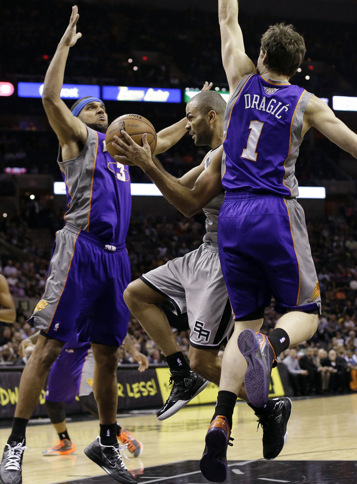 San Antonio Spurs' Tony Parker, center, of France, is caught between Phoenix Suns defenders Jared Dudley (3) and Goran Dragic (1) during the first quarter of an NBA basketball game, Saturday, Jan. 26, 2013, in San Antonio, Texas. (AP Photo/Eric Gay)