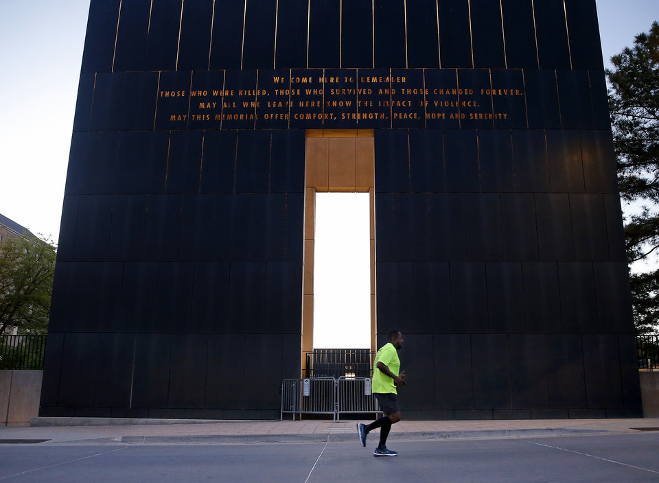 Photo - Barry Carrington runs in front of the 9:03 gate on the course of the Oklahoma City Memorial Marathon in Oklahoma City,  Sunday, April 26, 2020.  The 20th Oklahoma City Memorial Marathon was delayed until October because of Covid-19. [Sarah Phipps/The Oklahoman]