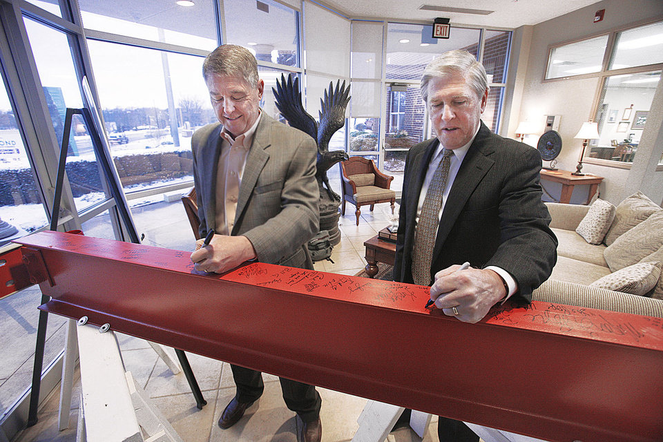 Photo - Gary Bartley and Nick Massey, both of Edmond, sign a steel beam on display in the lobby of the Edmond  Economic Development Authority building on Monday. Photo by Paul B. Southerland, The Oklahoman