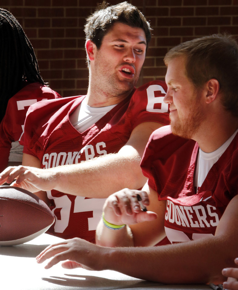 Photo - Sooner linemen Gabe Ikard (64) and Austin Woods (right) sign autographs during the Meet the Sooners event inside Gaylord Family/Oklahoma Memorial Stadium at the University of Oklahoma on Saturday, Aug. 4, 2012, in Norman, Okla.  Photo by Steve Sisney, The Oklahoman