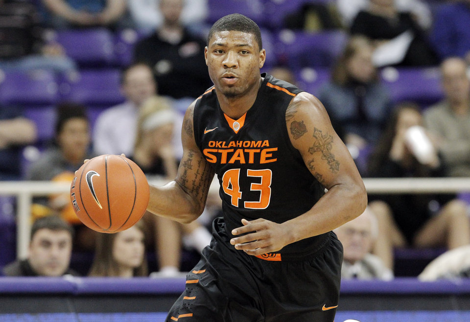 Photo - Oklahoma State guard Marcus Smart (43) looks for space against the TCU defense in the first half of an NCAA college basketball game, Monday, Feb. 24, 2014, in Fort Worth, Texas. (AP Photo/Brandon Wade)