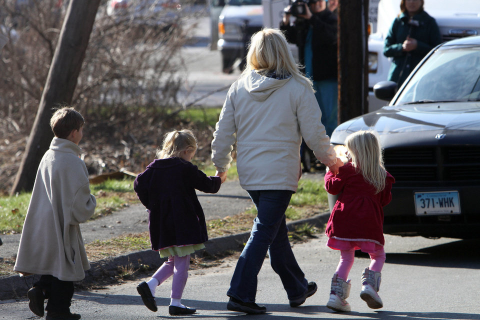 Photo - Parents walk away from the Sandy Hook Elementary School with their children following a shooting at the Newtown, Conn. school where authorities say a gunman opened fire, leaving 27 people dead, including 20 children, Friday, Dec. 14, 2012.  (AP Photo/The Journal News, Frank Becerra Jr.) MANDATORY CREDIT, NYC OUT, NO SALES, TV OUT, NEWSDAY OUT; MAGS OUT ORG XMIT: NYWHI115