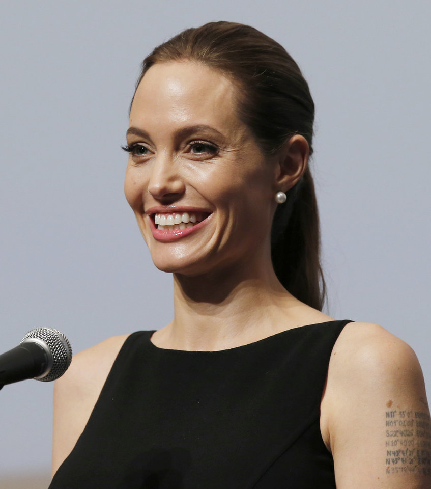 Photo - Angelina Jolie smiles as she delivers a statement before screening her film