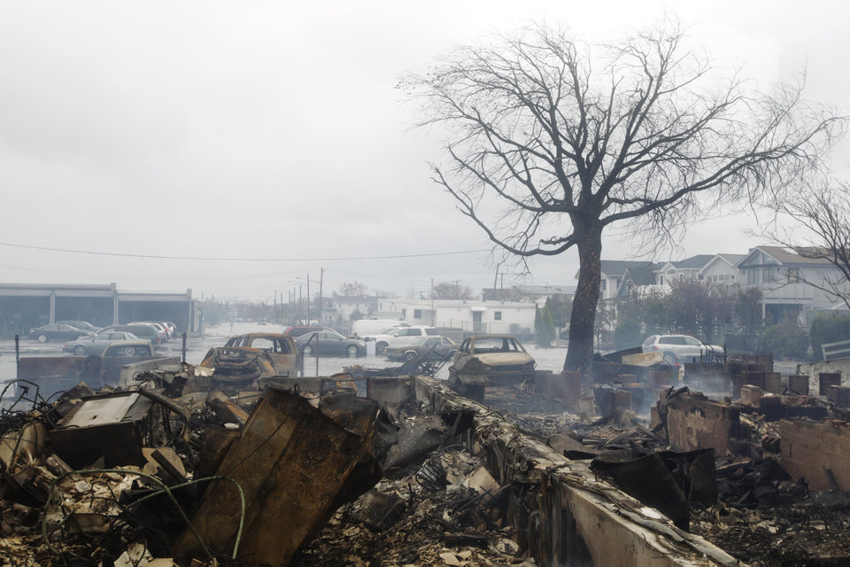 Photo -   Homes damaged by a fire at Breezy Point are shown, in the New York City borough of Queens Tuesday, Oct. 30, 2012, in New York. The fire destroyed between 80 and 100 houses Monday night in the flooded neighborhood. More than 190 firefighters have contained the six-alarm blaze fire, but they are still putting out some pockets of fire. (AP Photo/Frank Franklin II)