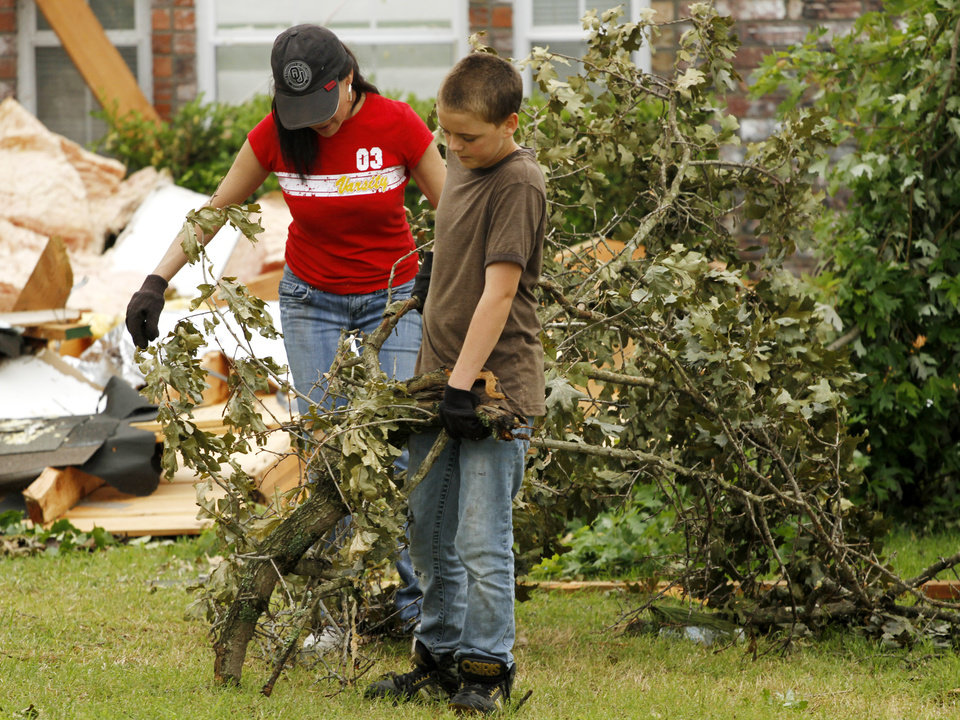 Brighton Godwin and his mother Catherine Godwin work to carry a large broken branch to the street in the Dripping Springs Estates Saturday, May 15, 2010. Saturday hundreds of volunteers went into areas that had been affected by last week's tornadoes to help clear debris. Photo by Doug Hoke, The Oklahoman.