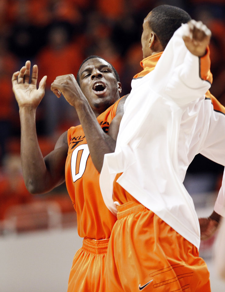Photo - OSU's Jean-Paul Olukemi (0) celebrates with teammate Jarred Shaw (1) during the men's college basketball game between Oklahoma State University (OSU) and Kansas State University (KSU) at Gallagher-Iba Arena in Stillwater, Okla., Saturday, January 8, 2011. OSU won, 76-62. Photo by Nate Billings, The Oklahoman