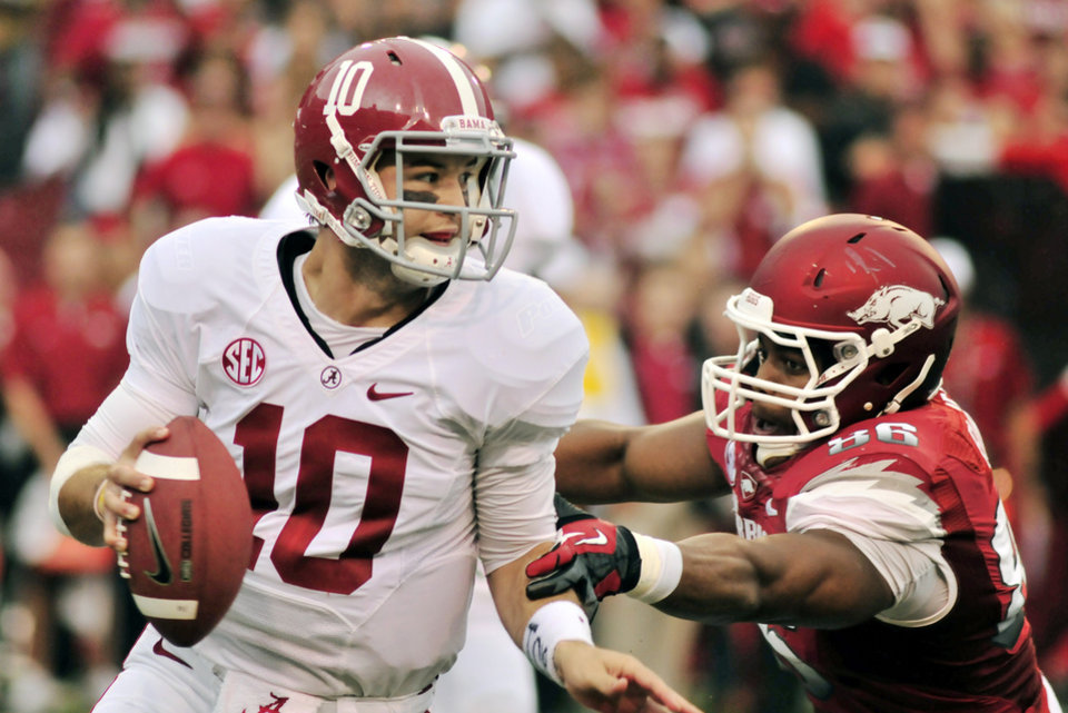 Photo -   Alabama quarterback AJ McCarron (10) looks for a receiver as he is pressured by Arkansas defensive end Trey Flowers (86) during the first half of an NCAA college football game in Fayetteville, Ark., Saturday, Sept. 15, 2012. (AP Photo/April L. Brown)