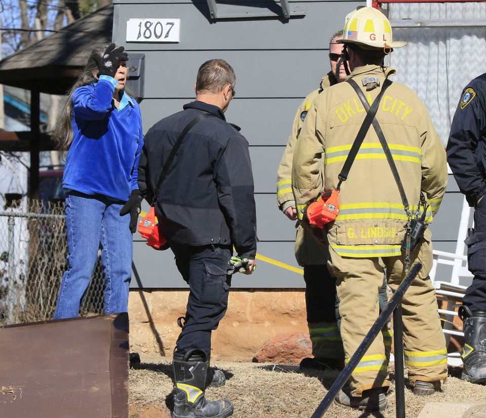 Photo -  The neighbor of a woman who was found dead inside a burning duplex on Friday speaks to Oklahoma City police and fire officials at the scene. [Photo by Paul Hellstern, The Oklahoman]