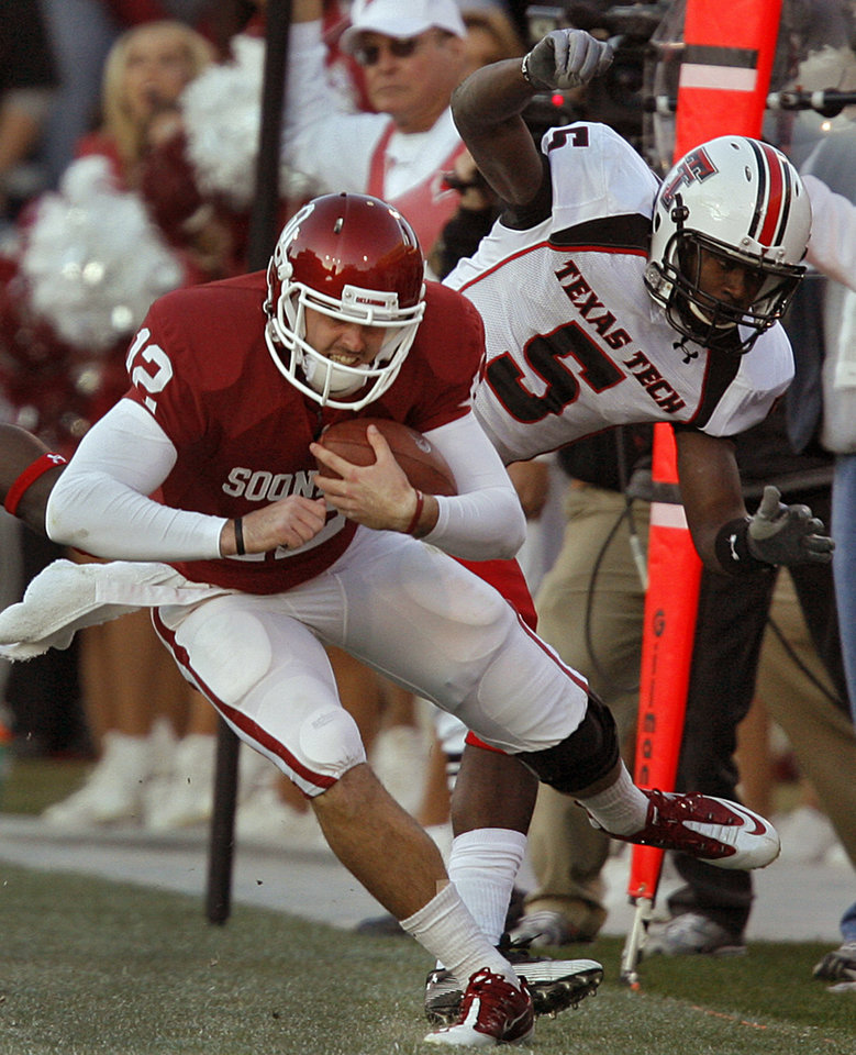 Photo - Oklahoma's Landry Jones (12) is knocked out of bounds by Tre' Porter (5) during the second half of the college football game between the University of Oklahoma Sooners (OU) and the Texas Tech Red Raiders (TTU) at the Gaylord Family Memorial Stadium on Saturday, Nov. 13, 2010, in Norman, Okla.  Photo by Chris Landsberger, The Oklahoman