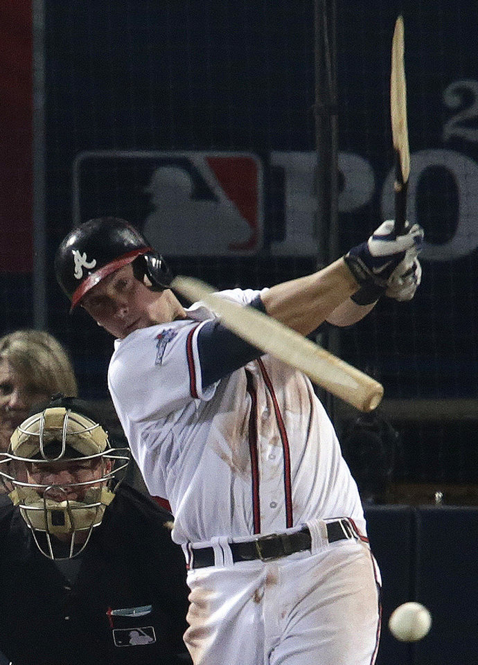 Photo - Atlanta Braves' Chris Johnson hits a broken-bat single against the Los Angeles Dodgers in the seventh inning of Game 2 of the National League division series on Friday, Oct. 4, 2013, in Atlanta. (AP Photo/Dave Martin)