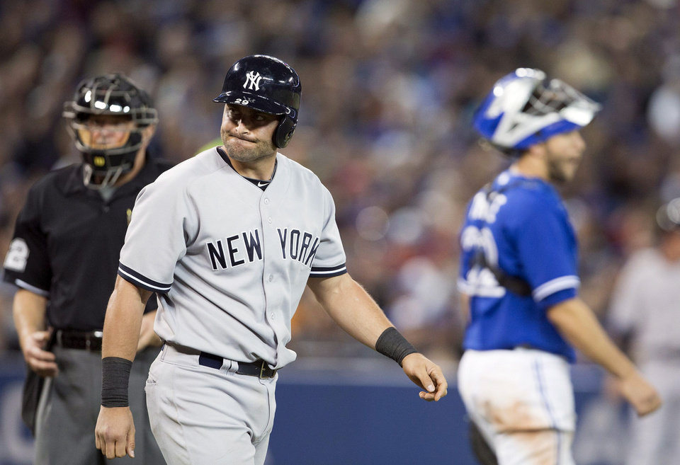 Photo - New York Yankees' Francisco Cervelli walks toward first base after getting hit by a pitch by Toronto Blue Jays starting pitcher R.A. Dickey during the fifth inning of a baseball game in Toronto on Saturday, April 5, 2014. (AP Photo/The Canadian Press, Peter Power)