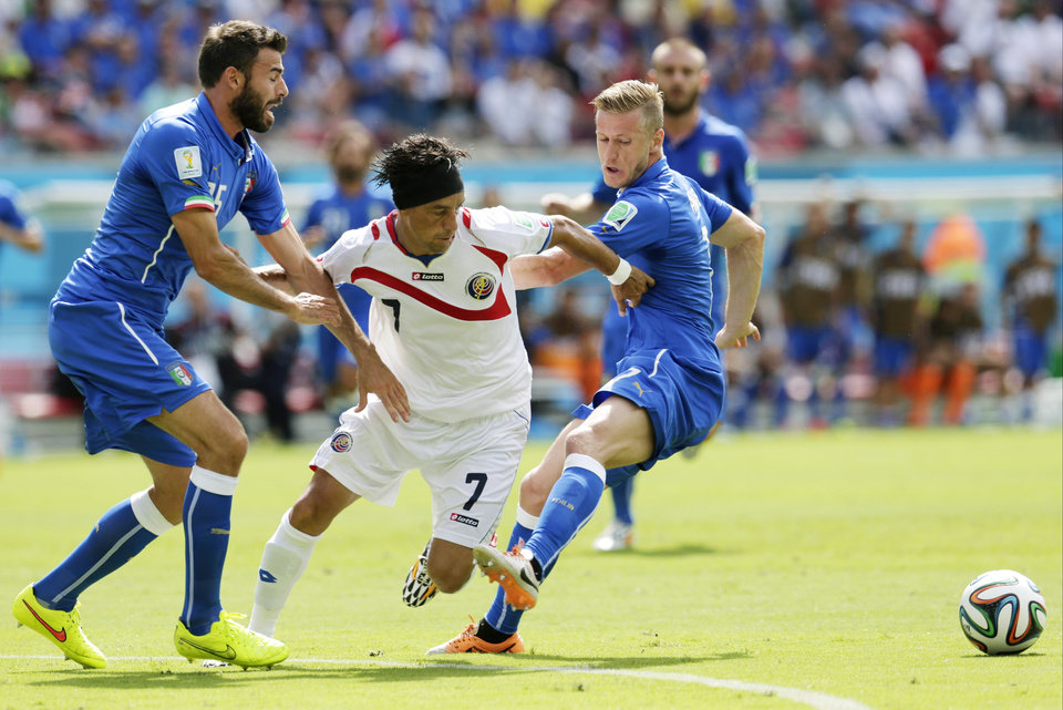 Photo - Italy's Andrea Barzagli, left, and Ignazio Abate, right hold Costa Rica's Christian Bolanos as he tries to reach the ball during the group D World Cup soccer match between Italy and Costa Rica at the Arena Pernambuco in Recife, Brazil, Friday, June 20, 2014.  (AP Photo/Petr David Josek)